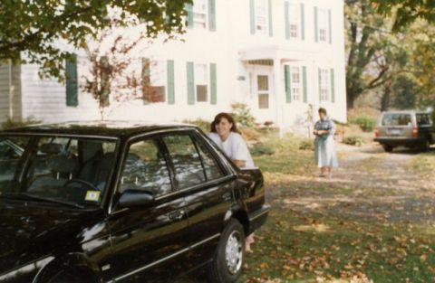 black mazda 323 in front of white farmhouse