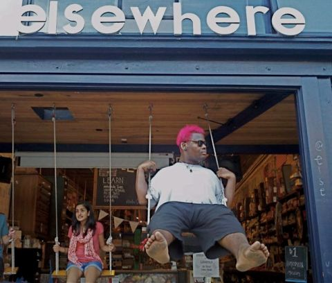 man with pink hair on a swing in the window of the Elsewhere Living Museum