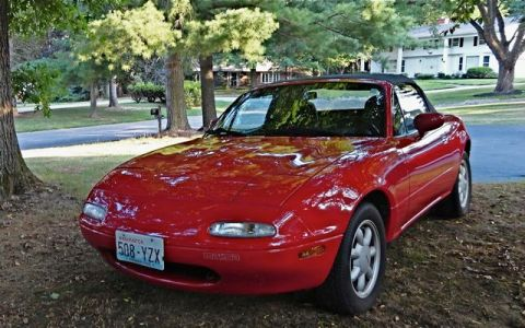 red miata convertible parked under a tree