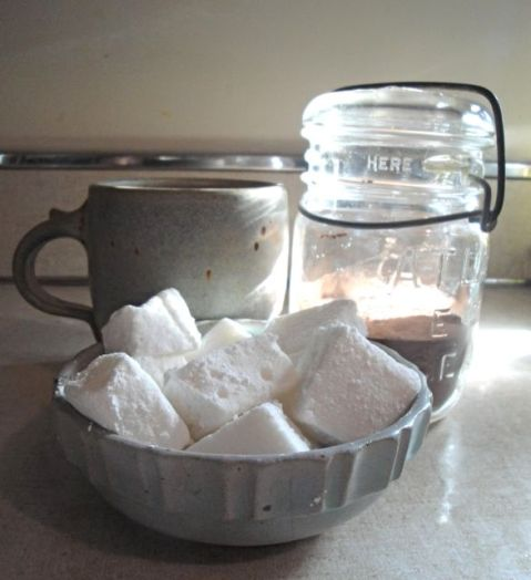 bowl with marshmallows glass jar with cocoa mix and mug